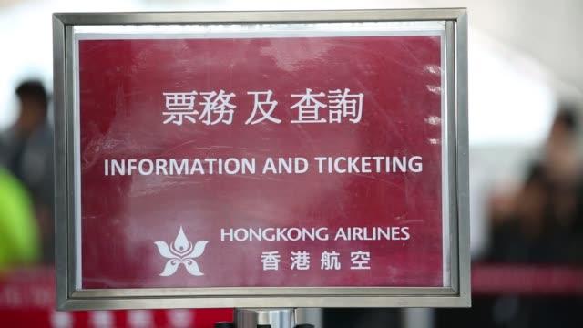 passengers walk past a hong kong airlines ltd signage displayed on a wall near a hong kong airlines ltd check in counter at hong kong international... - flugpassagier stock-videos und b-roll-filmmaterial
