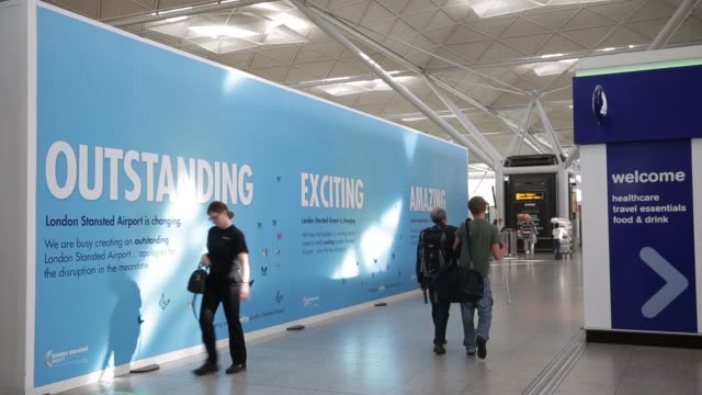 stockvideo's en b-roll-footage met passengers walk past temporary hoardings at stansted airport operated by manchester airports group in london uk on wednesday aug 7 close shot... - reclamebord commercieel bord