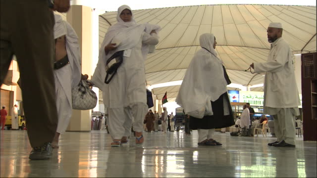 passengers walk through hajj terminal in saudi arabia. - hajj stock-videos und b-roll-filmmaterial