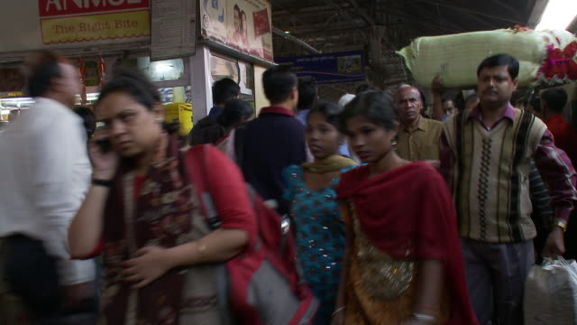 passengers walk through the crowded howrah station after arriving on a train. - bahnreisender stock-videos und b-roll-filmmaterial
