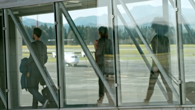 passengers walking across a glass boarding bridge at the airport - luggage stock videos & royalty-free footage