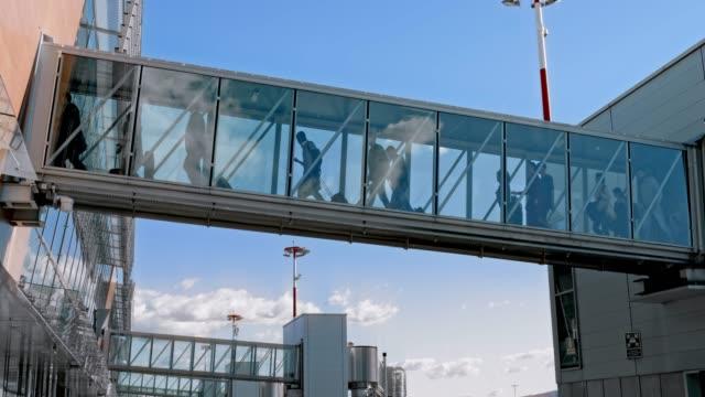 ld passagiere zu fuß über ein glas brücke einsteigen an bord des flugzeugs - fluggastbrücke stock-videos und b-roll-filmmaterial