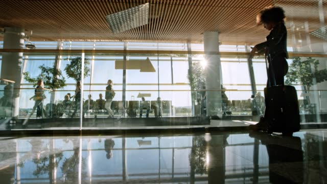 DS Passengers walking in the airport terminal with sun shining through large glass windows
