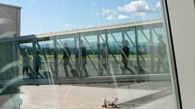 ld-passagiere zu fuß auf der bordkarte brücke - fluggastbrücke stock-videos und b-roll-filmmaterial