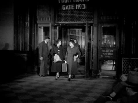 Passengers walking out from 'Gate 03' in Union Passenger Terminal VS Worker unloading luggage off locomotive train passengers including Westbrook Van...