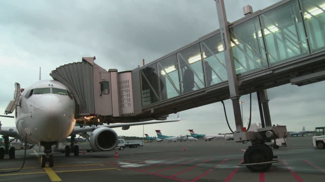 ws passengers walking through boarding bridge at findel airport / luxembourg - 乗り込む点の映像素材/bロール