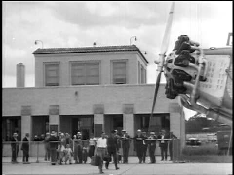 stockvideo's en b-roll-footage met b/w 1927 passengers walking towards airliner from terminal / newsreel - 1927