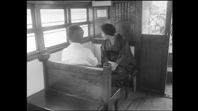 Passengers watch as a Tsukuda ferryboat approaches a destination pier.