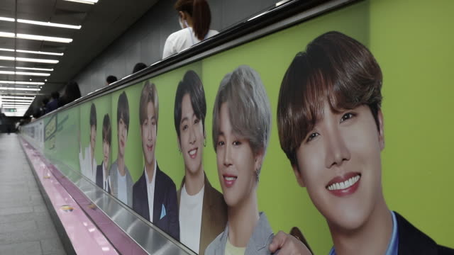 vidéos et rushes de passengers wearing masks riding moving walkway with advertisement of bts band at a subway station, in seoul, south korea, on friday, september 18,... - k pop