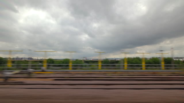 a passengers window view from a moving train passes by the end of gatwick airports runway and continues to pull into and stop at gatwick airports train station - zugperspektive stock-videos und b-roll-filmmaterial