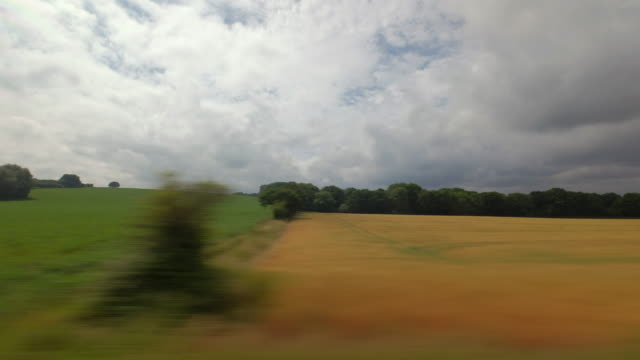 A passengers window view from a moving train traveling through the English rural countryside passes a wheat field ready for harvest
