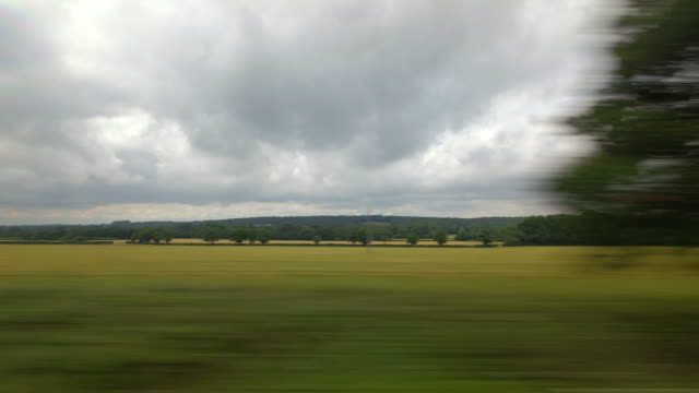 A passengers window view from a moving train traveling through the rural English countryside passes a level road crossing at speed