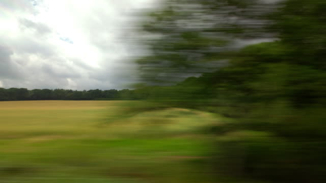 a passengers window view from a moving train traveling through the rural english countryside passes two small farm cottages nestled in trees - zugperspektive stock-videos und b-roll-filmmaterial