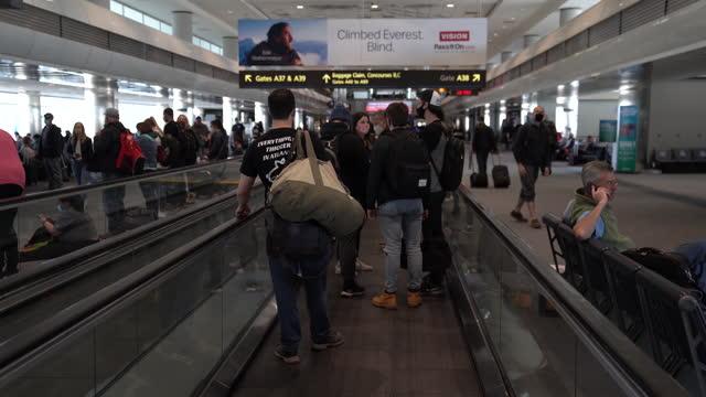 stockvideo's en b-roll-footage met passengers with baggage onmoving walkway at denver international airport in denver, colorado, u.s., on thursday, april 8, 2021. - dia