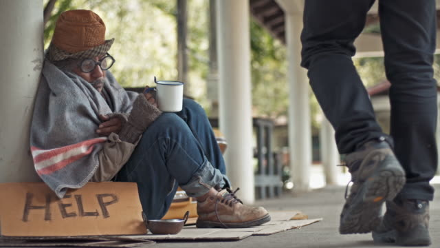 a passer by giving a money to a homeless person begging - beggar stock videos & royalty-free footage