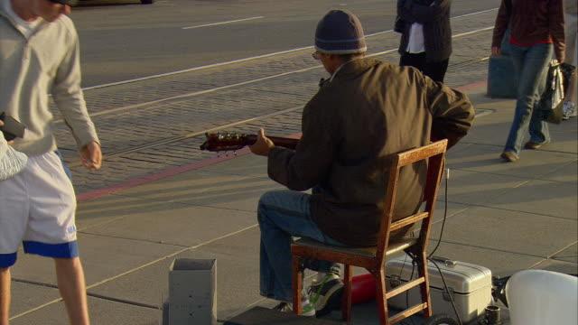 MS Passerby making donation to street performer playing guitar at Fisherman's Wharf, San Francisco, California, USA