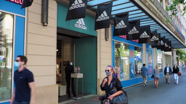 passerby wearing a face mask, seen walking in front of an adidas store which is open, on may 28, 2020 in paris, france. the coronavirus pandemic has... - adidas stock videos & royalty-free footage