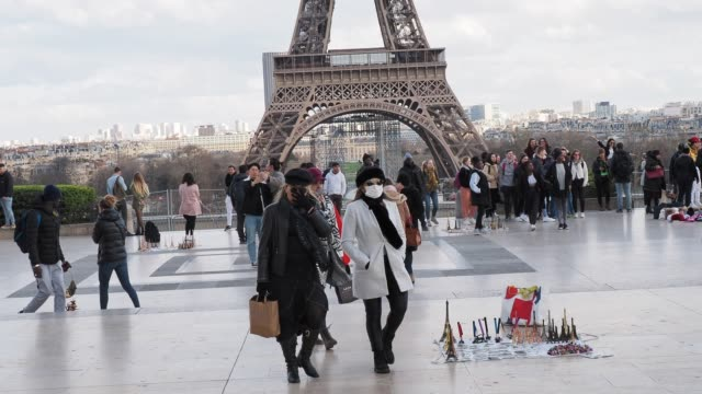a passerby wears a protective face mask at place du trocadero in front of the eiffel tower on march 12 2020 in paris france due to a sharp increase... - human face stock videos & royalty-free footage