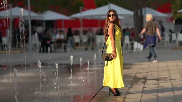 passerby wears sunglasses, a neon yellow long dress, a bag, black high heeled pointed shoes, during the 78th venice international film festival on... - brown hair stock videos & royalty-free footage