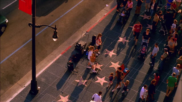stockvideo's en b-roll-footage met passerbyers walking past musicians perfoming on hollywood walk of fame / hollywood, los angeles, california - hollywood walk of fame