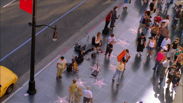 Passerbyers watching young musicians on break from perfoming on Hollywood Walk of Fame / Hollywood, Los Angeles, California