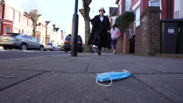 passers by celebrating purim pass a discarded face mask on the pavement during purim on february 26, 2021 in london, england. last year's purim... - religion stock videos & royalty-free footage