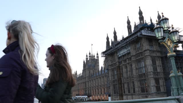 passers by on westminster bridge enjoy the view of the houses of parliament, the city skyline and the river thames on february 20th, 2021 in london,... - ウェストミンスター宮殿点の映像素材/bロール