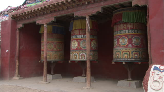 passers-by spin a prayer wheel in a tibetan temple. - philosophy stock videos & royalty-free footage