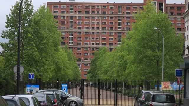 vidéos et rushes de passers-by walk in a park, as background a red brick social housing building on may 6, 2021 in ivry sur seine, france. the estate maurice-thorez was... - problème de logement