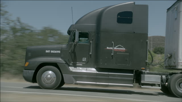 vídeos de stock, filmes e b-roll de ts suv passing a semi-truck down a desert highway / los angeles, california, united states - formato letterbox