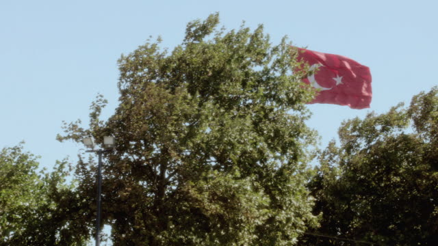 POV Passing a waving Turkish flag rising above tall trees / Istanbul, Turkey