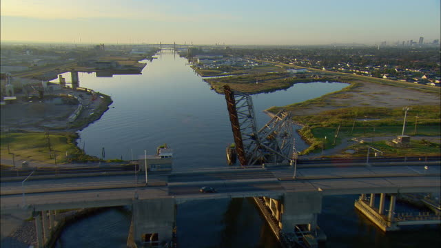 WS POV AERIAL Passing along industrial canal as car crosses on bridge at dawn / New Orleans, Louisiana, USA