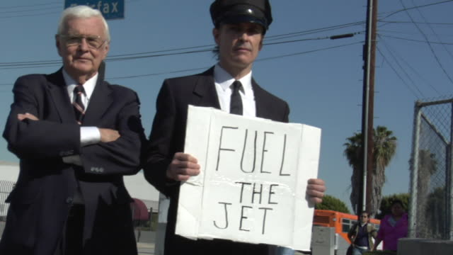 POV Passing businessman and his driver holding sign saying 'Fuel the Jet' on street, Los Angeles, California, USA