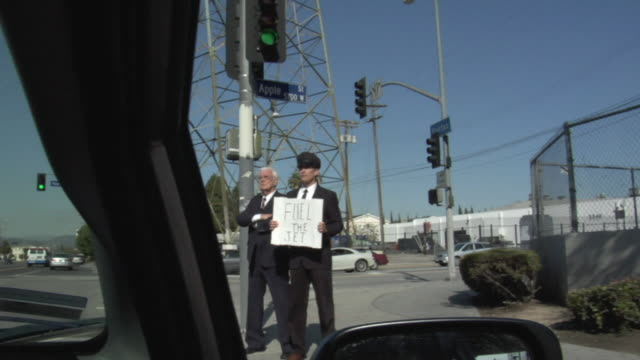 pov passing businessman and his driver holding sign saying 'fuel the jet' on street, los angeles, california, usa - see other clips from this shoot 1458 stock videos and b-roll footage
