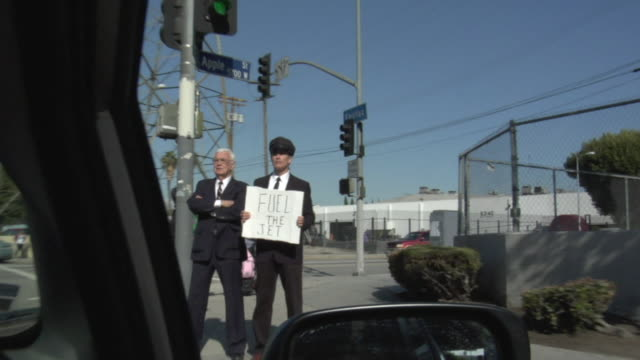 vídeos de stock, filmes e b-roll de pov passing businessman and his driver holding sign saying 'fuel the jet' on street, los angeles, california, usa - sátira