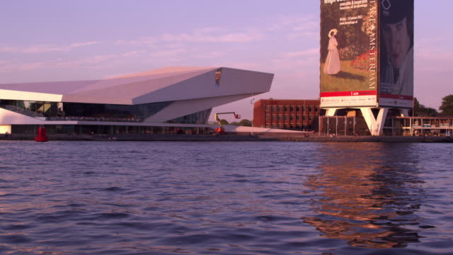 passing by a contemporary building along the amsterdam shoreline - spruchband stock-videos und b-roll-filmmaterial