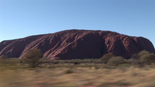 SIDE POV Passing by Ayers Rock (Uluru), Uluru-Kata Tjuta National Park, Northern Territory, Australia