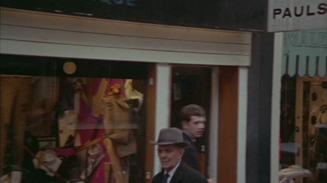 1966 SIDE POV Passing by shops and people walking on sidewalk / London, United Kingdom