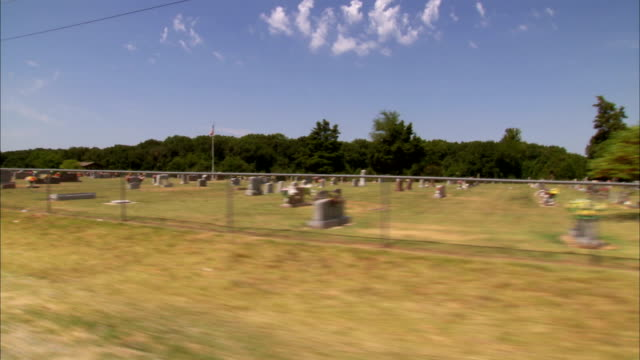 passing cemetery w/ gravestones tombstones ok rural countryside country - oklahoma stock videos & royalty-free footage
