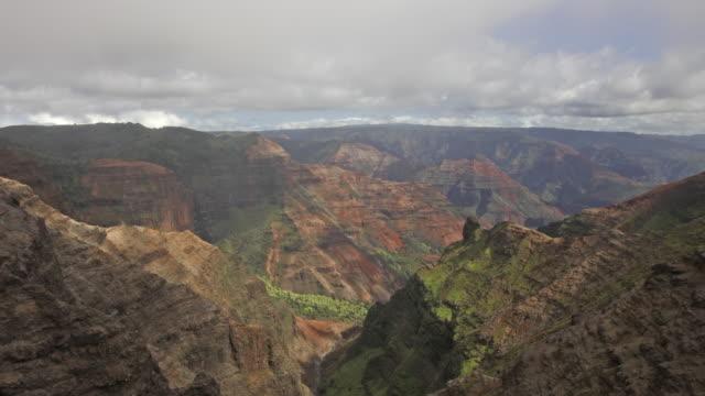 passing clouds over waimea canyon in kauai, hawaii create shadows on the terrain. - 峡谷点の映像素材/bロール