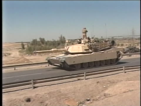 passing convoy vehicle of m1a1 abrams main battle tank sits at rest on the road. - al fallujah stock videos & royalty-free footage