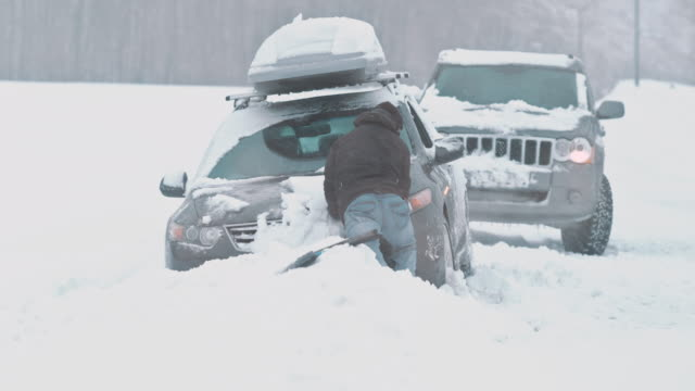 Passing driver helping a man get his car out of snow
