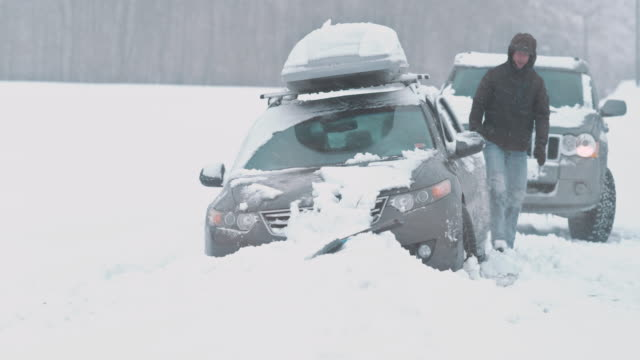 passing driver helps by pushing the car out of snow - mode of transport stock videos & royalty-free footage