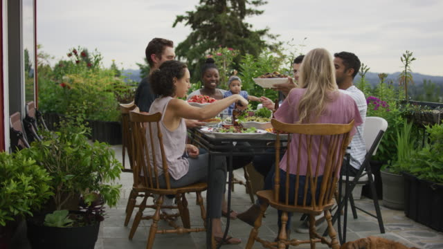 passing food around at an outdoor dinner party - mixed race person stock videos & royalty-free footage