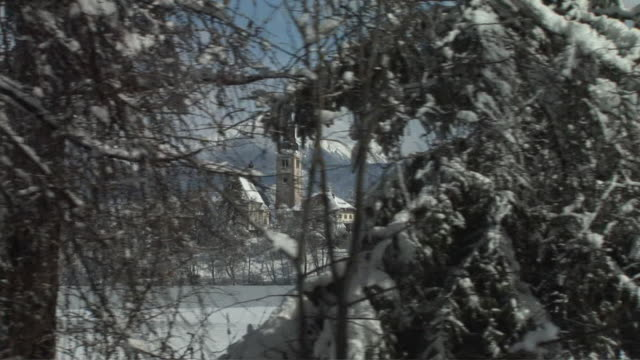 side pov, passing island on lake bled with church of the assumption of mary, snow covered trees in foreground, gorenjska, slovenia - lago di bled video stock e b–roll