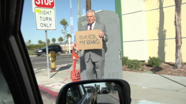 pov passing man holding sign saying 'your risk my reward' on street, los angeles, california, usa - 2009 video stock e b–roll