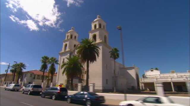 side pov, passing saint augustine cathedral, tucson, arizona, usa - fächerpalme stock-videos und b-roll-filmmaterial