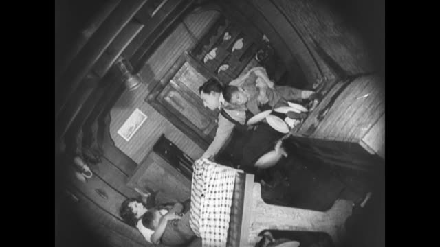 1921 passing speedboat knocks man's (buster keaton) boat dramatically causing him to nail the ship's wheel in place - schwanken stock-videos und b-roll-filmmaterial