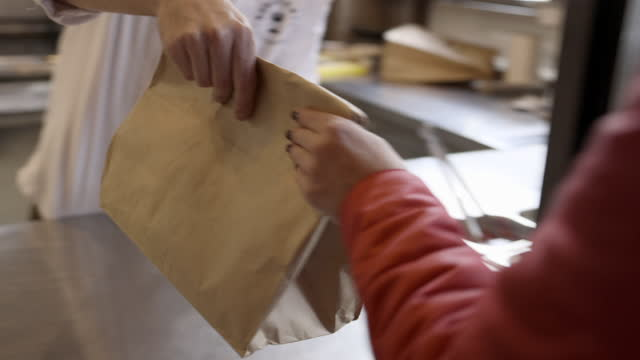 passing take out in paper bag over the counter in the restaurant - paper bag stock videos & royalty-free footage