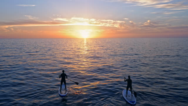 aerial passing two people paddling their sups in adriatic sea at sunset - salvataggio video stock e b–roll